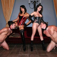 Dark-haired Dominas Adriana Lynn and Mia Li manhandle collared and naked stud submissives