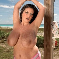 Dark haired MILF Arianna Sinn flaunts her monster-sized breasts in the outdoors with the ocean in glance