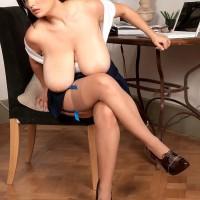 Brunette MILF Arianna Sinn sets her huge boobies free in semitransparent stockings and stilettos