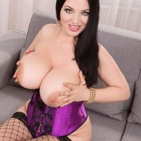 Dark haired MILF Joana Bliss revealing giant melons in lingerie and ebony fishnet stockings