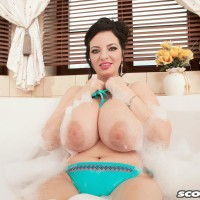 Dark-haired MILF Joana Bliss letting gigantic all-natural breasts loose from swimsuit in bathtub