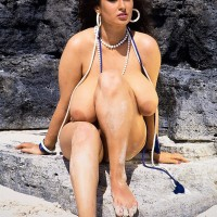Dark haired MILF Lisa Phillips touts her gigantic titties and ass on a sandy beach