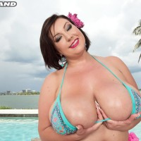 Brunette MILF Paige Turner rubbin' humungous bathing suit covered juggs outdoors on beach
