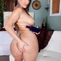 Brown-haired MILF Vanessa Luna flashing hefty butt and tats before unsheathing massive titties