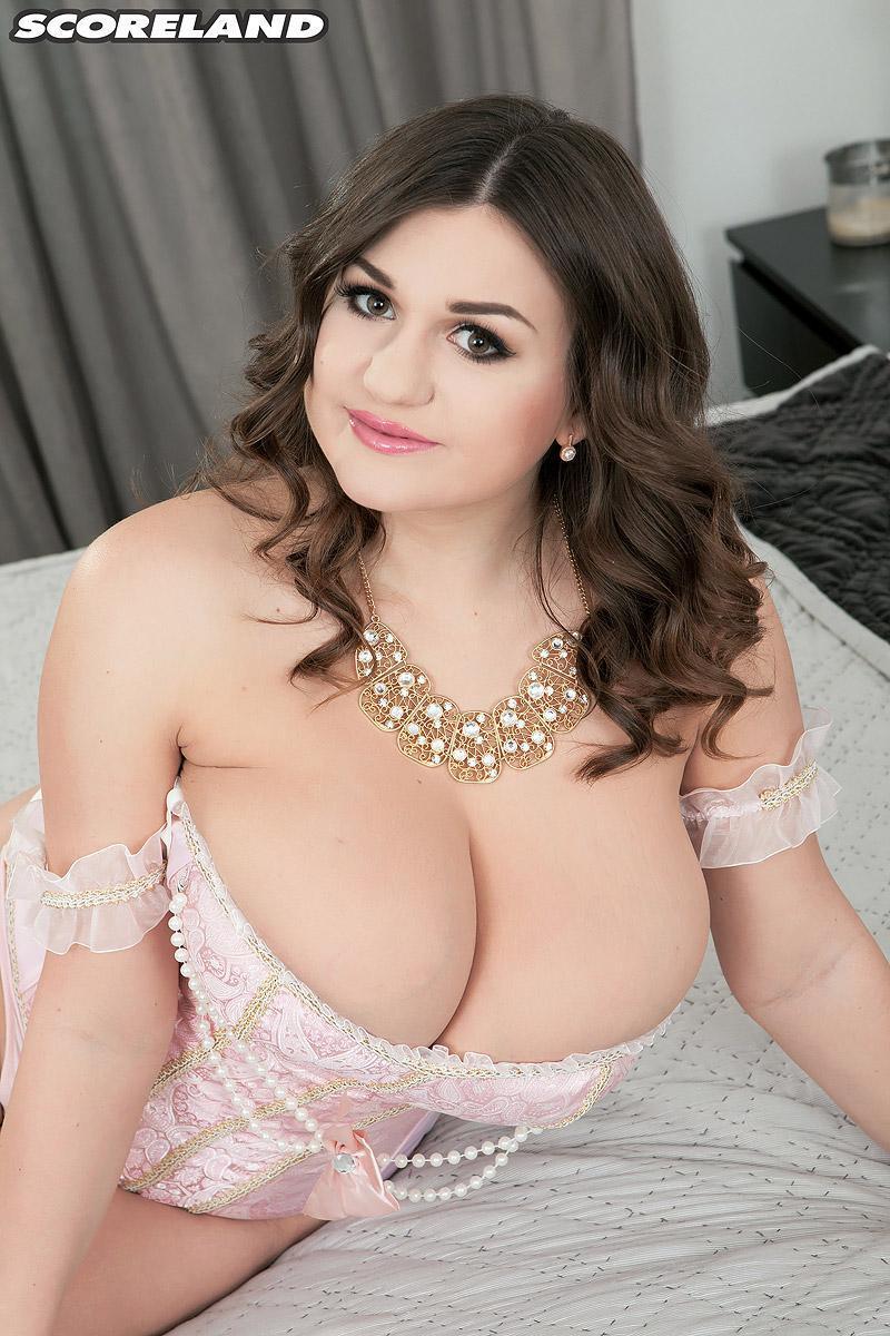 Dark haired babe Demmy Blaze modelling in fantastic white lingerie and hose on bed