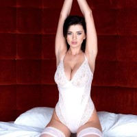 Brunette solo female Sha Rizel bares her humungous tits from onesie in milky stockings