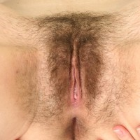 Brunette stunner undressing nude to spread and finger boink fur covered slit on bed