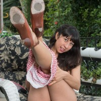Dark-haired solo female Vivi Marie showing off wooly armpits and spread pussy outdoors