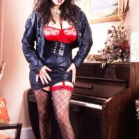 Dark-haired solo model Jeannine Oldfield extracts her massive boobs in leather and hose