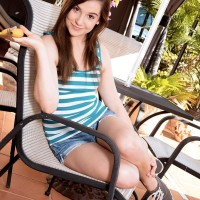 Brown-haired teenager Kasey Warner slurps a banana before exposing her smallish tits outdoors