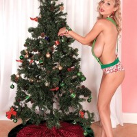 Huge-chested blonde MILF Venera displaying great legs in high heeled shoes by X-mas tree