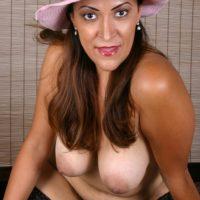 Bosomy mature dame in sun hat sheds high heels from nylon attired feet