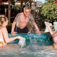 Chesty MILF lesbians Brandy Talore and April McKenzie providing handjob in pool