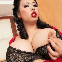 Oriental XXX star Tigerr Benson unsheathing immense tits from lingerie in a kitchen