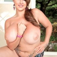 Plumper MILF model Terri Jane letting massive titties fall free from brassiere outdoors in high-heels