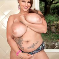 Plumper MILF model Terri Jane letting massive titties fall free from brassiere outdoors in high-heels