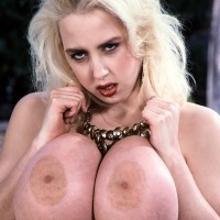 Old-school adult film starlet Letha Weapons highlights her enlargened breasts by a swimming pool
