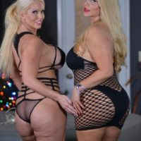 Bootylicious mature blonde Karen Fisher and her lezzie gf break out a sex toy on a bed