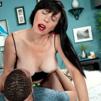Dark haired 50 plus MILF Raven Flight pulling out large boobs while seducing junior stud