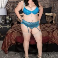 Brown-haired BBW Charlotte Angel sets her humungous titties free of lingerie on top of a bed