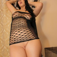 Black-haired Dominant Ashley posing about dungeon space partly naked in fetish apparel