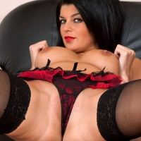 Black-haired experienced dame revealing humungous boobs and tempting caboose in tights and heels