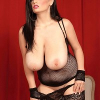 Dark-haired solo girl Arianna Sinn gobbles a nipple after uncovering her immense tits