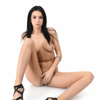 Brown-haired solo girl Foxxi Ebony strips to her high-heels before dildoing her bald gash
