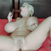 Enormous jugged platinum light-haired Claudia Marie sucks on a faux-cock while masturbating on a bed