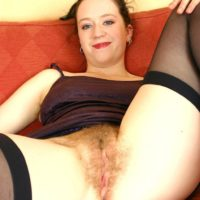 European first timer demonstrating unshaven pits before spreading wooly vag on couch