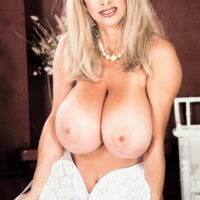 Notorious adult video starlet Alexis Enjoy uncups her hefty boobies in milky pantyhose and crimson pumps
