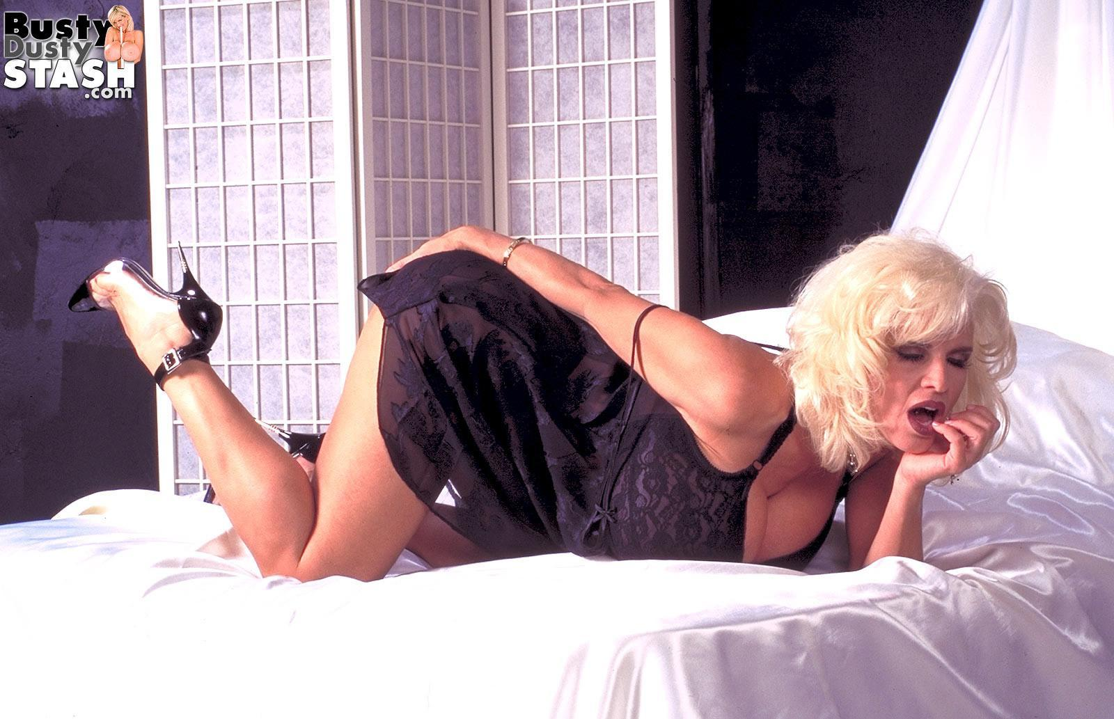 Notorious adult film starlet Chesty Dusty frees her immense breasts in semi-transparent panties and stilettos