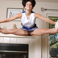 Supple female doffs a cheerleader uniform before playing with her vag while naked
