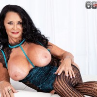 Grandma XXX film starlet Rita Daniels releases her giant breasts before slurping and jacking a faux-cock