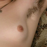 Hirsute European amateur with pierced hard nipples undressing to pose in the naked