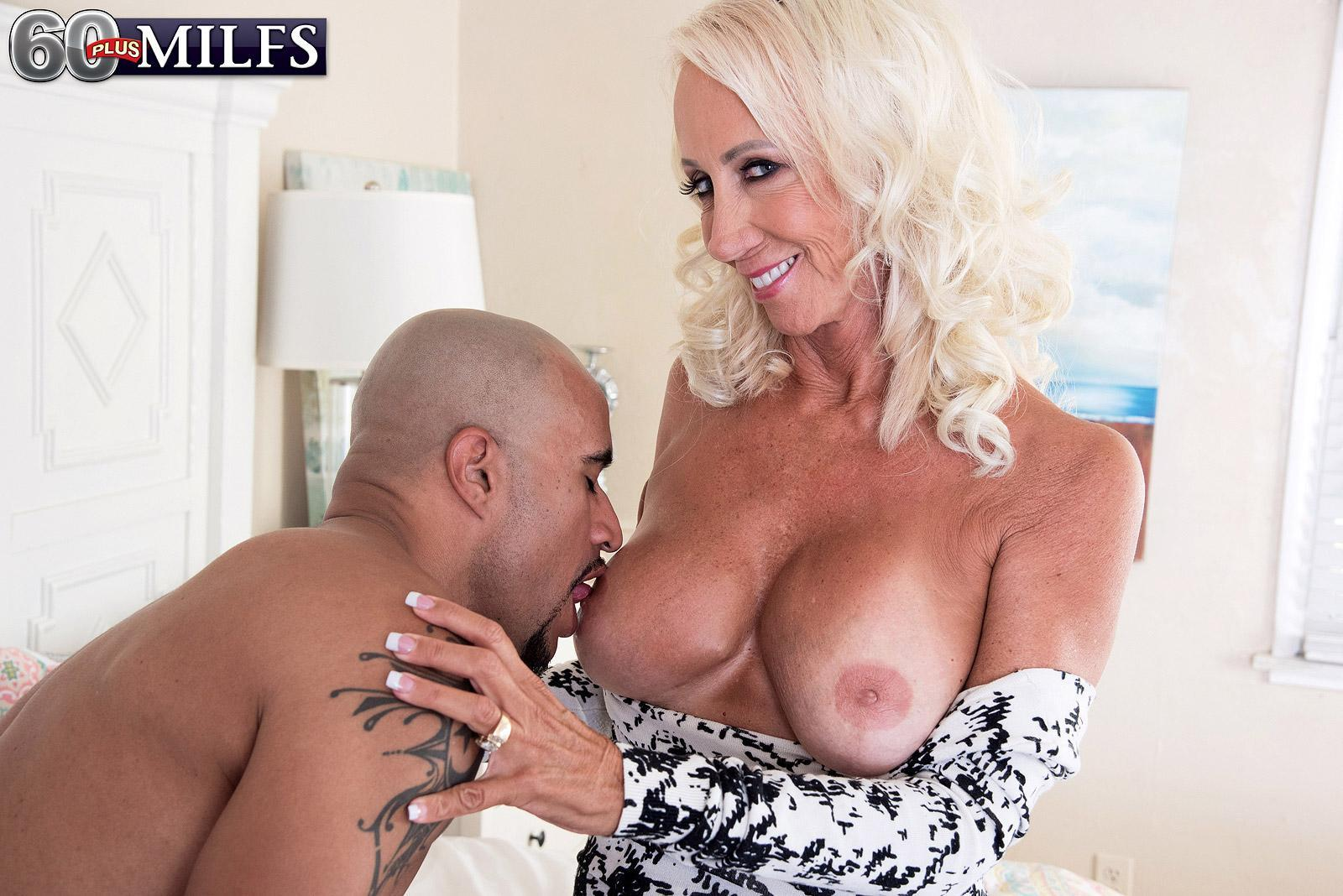 Seductive 60 plus MILF Madison Milstar tempts a younger ebony guy in a cock-squeezing fitting dress