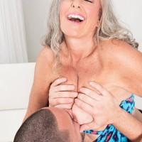Phat Sixty plus MILF Silva Foxx tempts a junior man by flashing her titties in a denim mini-skirt