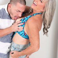 Mind-blowing Sixty plus MILF Silva Foxx seduces a junior guy by flashing her boobs in a denim microskirt