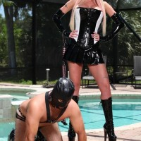seductive blonde wife Alexia Jordon sits astride a masked masculine sub in latex by the pool