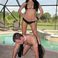 Enticing brunette Adriana Lynn makes a collared male submit to her will in stiletto boots
