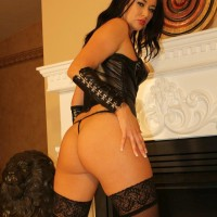 Uber-sexy black-haired Dominant Ashley plays with her swell nipples in leather and hose