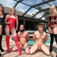 Irresistible females in latex clothing and hip high boots manhandle collared male submissives by a pool