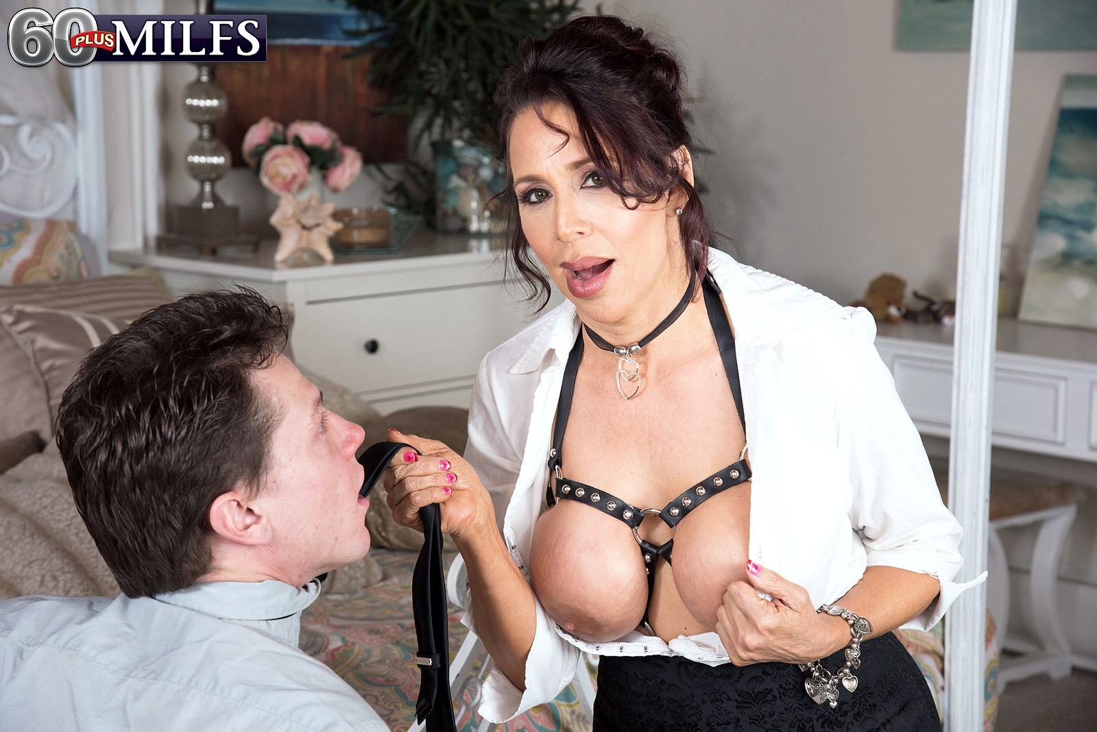 Hot grandmother Lisa Marie Heart entices a younger guy in a choker and limit bondage harness