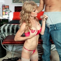 Enticing old broad Denise Day entices a junior stud in leather microskirt and hose