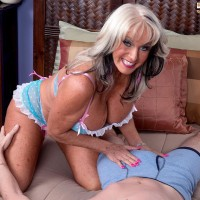 Provocative over Fifty MILF Sally D'Angelo flashing big breasts while seducing man for sex on bed