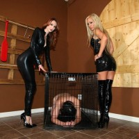 Latex garmented Dommes Zoey and Kendra jerking off confined and hooded male slave