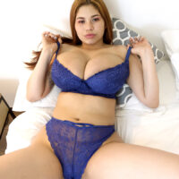 Latina redhead Lucy Rodriguez plays with her immense boobs while getting nude on a bed