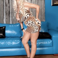 Leggy yellow-haired MILF Brittany O'Neil loosing large knockers for black stud on leather sofa