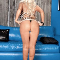 Long-legged yellow-haired MILF Brittany O'Neil whipping out huge boobies for black stud on leather sofa