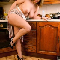 Mature blond housewife lets her gigantic all-natural hooters free in her kitchen